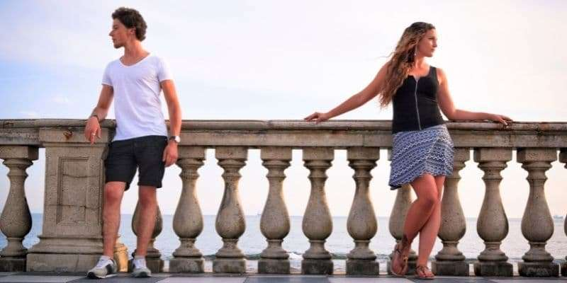 man and woman standing apart facing away from each other on a bridge - cancer and sagittarius